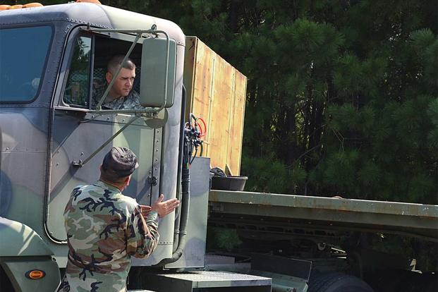 Sgt. 1st Class Matthew Caster takes instructions about how to properly parallel park a large truck Aug. 2 as part of a commercial driver's license pilot program on Fort Lee. (Photo Credit: Amy Perry)