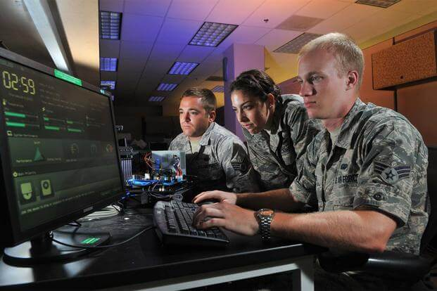 Three airmen perform cyber operations at Lackland Air Force Base, Texas, Aug. 1, 2012. (U.S. Air Force/Boyd Belcher)