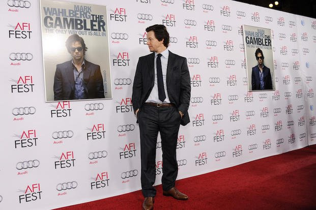 "producer of ""The Gambler"" looks at a poster for the film as he poses at the premiere at AFI Fest 2014 on Monday, Nov. 10, 2014, in Los Angeles"