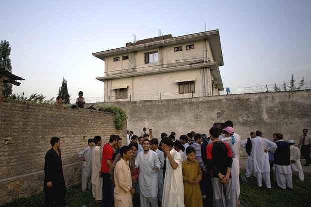 In this May 3, 2011 file photo, local residents gather outside a house, where al-Qaida leader Osama bin Laden was caught and killed in Abbottabad, Pakistan.