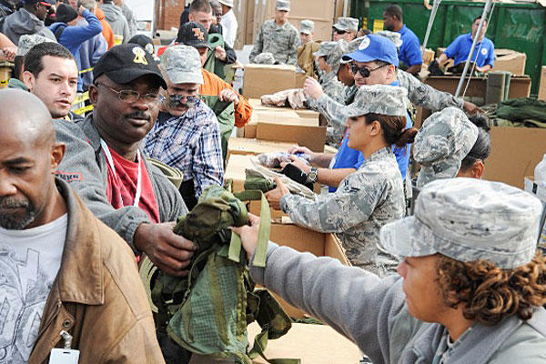 Airmen from the 59th Medical Wing pass out free gear to homeless veterans during the 16th annual American GI Forum Veterans Stand Down. The event was organized by the National Veterans Outreach Program. (U.S. Air Force photo/Staff Sgt. Kevin Iinuma)