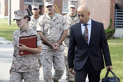 In this Aug. 21, 2014, file photo, defense attorneys 1st Lt. Brittaney Bennett, left, and Haytham Faraj, right, escort Cpl. Wassef Ali Hassoun, center, to his Article 32 hearing at Camp Lejeune, N.C. John Althouse/Jacksonville Daily News via AP
