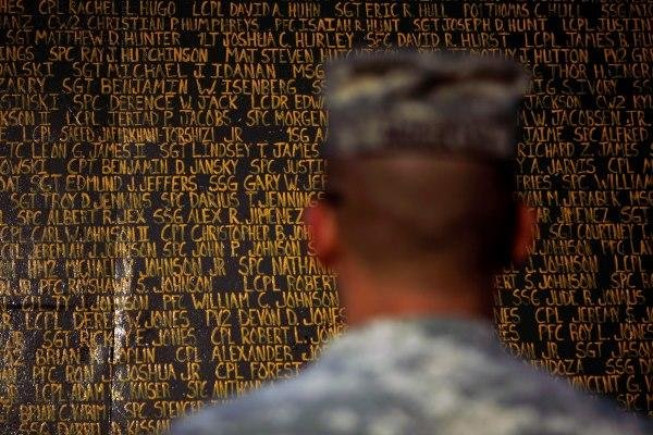 In this May 6, 2010 file photo, Sgt. Kevin McCulley stands in front of a monument bearing the names of more than 4,300 U.S. service members killed in Iraq since the 2003 invasion, at Forward Operating Base Warrior in Kirkuk. (AP Photo/ Maya Alleruzzo)