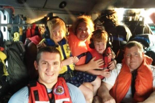 A rescue swimmer from Coast Guard Air Station Elizabeth City, N.J., poses with passengers aboard an MH-60 Jayhawk helicopter Monday, July 20, 2015. The crew hoisted six passengers after their boat ran aground in Wachapreague, Va. (US Coast Guard photo)