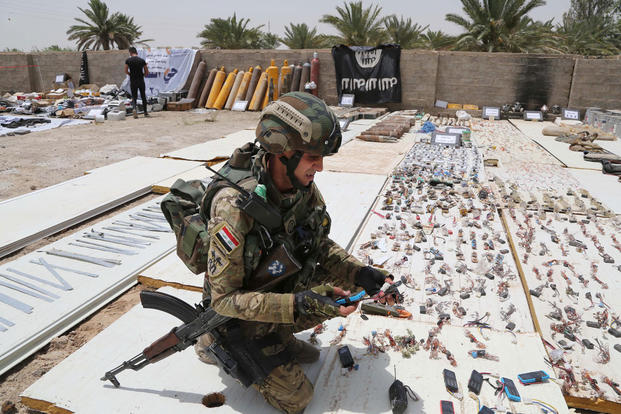 An Iraqi soldier picks up items on display with weapons and ammunition confiscated after security forces regained control of the towns of al-Karma and Saqlawiyah near Fallujah, at al-Taji Camp north of Baghdad, Iraq, July 10, 2015. Karim Kadim/AP