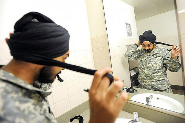 Spc. Simranpreet Singh Lamba, a combat medic, demonstrates tying a 5-meter-long turban May 23, 2011. Lamba's religion asks that he never cut his hair. He was the first enlisted Sikh soldier in more than three decades. Ingrid Barrentine/Northwest Guardian