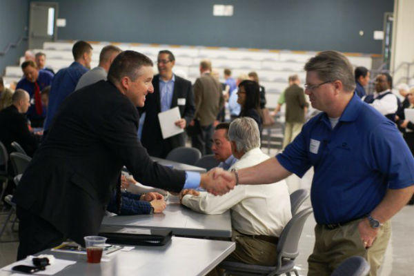 Steve Nolen, chief of planning and environmental division, shakes hands with a business representative during the Meet the Corps Day event