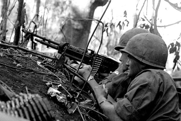 Troops lay down covering fire with an M-60 machine gun during the Vietnam War. (DoD photo)