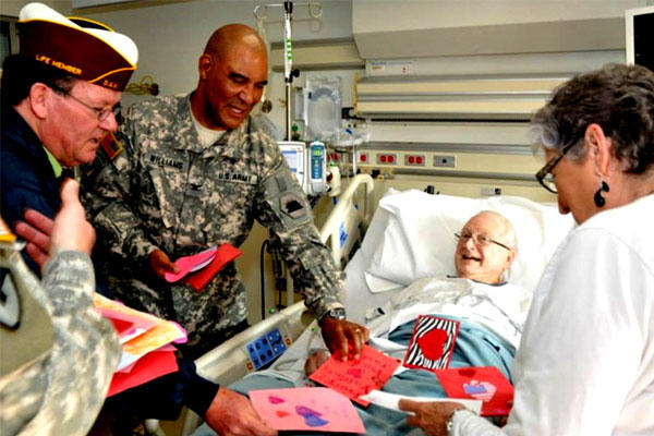 Visitors share valentines with a VA patient last February during National Salute to Veteran Patients Week. (VA photo)