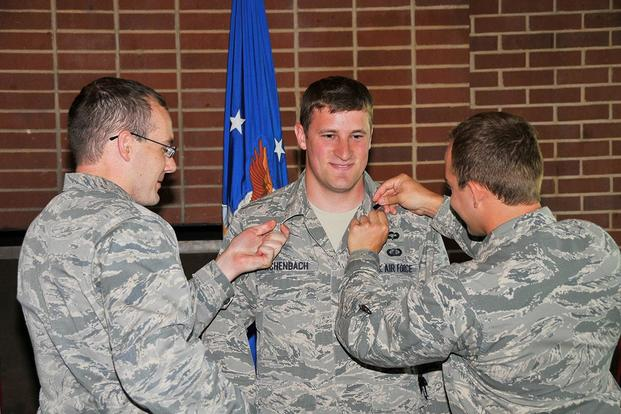 First Lt. Joseph Achenbach (center) is pinned by 1st Lt. Benjamin Hoff (left) and 1st Lt. Chance Johnson at a promotion ceremony. (U.S. Air Force/Jacqueline Cowan)