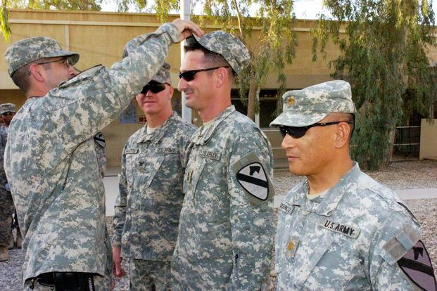 First Sgt. John Palido presents Master Sgt. Kenneth Stone with his new patrol cap during his promotion ceremony on Forward Operating Base Marez. (U.S. Army/Sgt. Chris Kozloski)