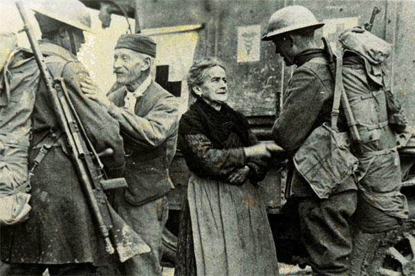 "American soldiers help French citizens after their town is liberated in 1918 by the 308th Infantry Regiment of the 77th Infantry Division, and the 166th Infantry Regiment of the 42nd Infantry ""Rainbow"" Division. (US Army photo)"