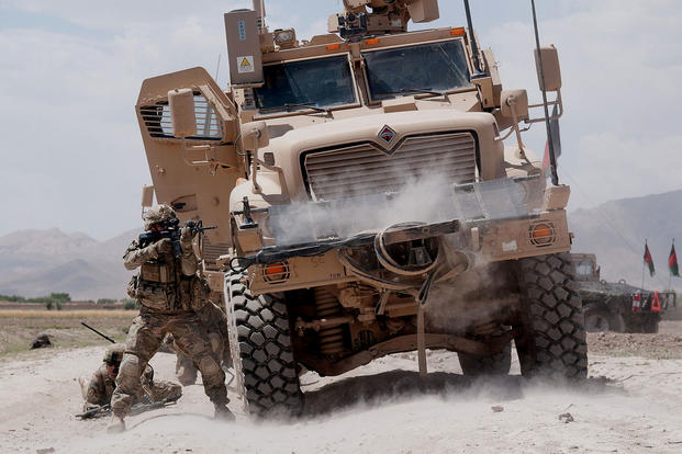 A U.S. Army paratrooper fires his M4 carbine at insurgents during a firefight in June 2012, in Ghazni Province, Afghanistan, using a Mine Resistant Ambush Protected vehicle for cover. (US Army photo/Michael MacLeod)