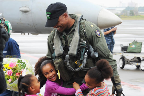 An Airman hugs his children