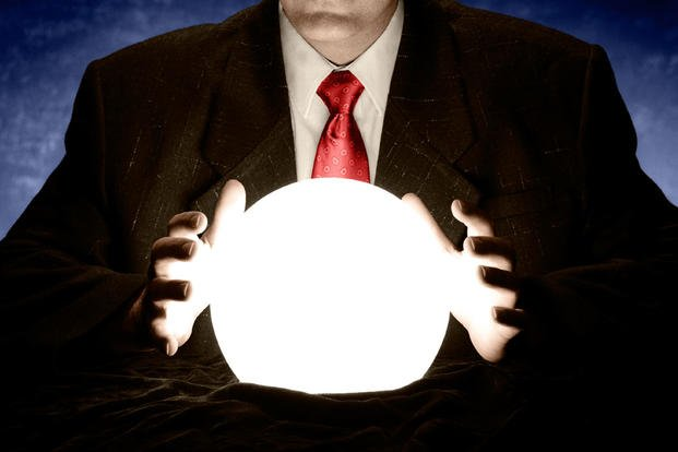 Businessman consulting glowing crystal ball (Image: Flickr/InfoWire.dk)