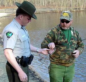 Conservation officer checking license by a lake.