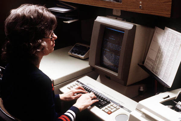 Woman typing at a computer.
