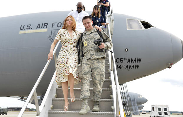 The Magnificent 7 movie actress Haley Bennett, wearing high heels, is helped by airman Josuha King as they disembark from a visit to a USAF KC-10 tanker prior to a USO-sponsored film premiere at Joint Base McGuire-Dix-Lakehurst, New Jersey, September 18, 2016. The cast members and director toured the flightline, greeted service members and met with military families to extend their appreciation for their service. USO Photo by Mike Theiler