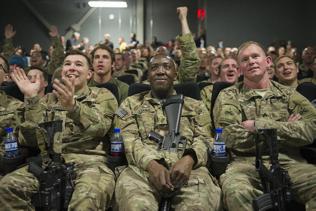 Service members deployed to Bagram Air Field, Afghanistan, clap and cheer as they prepare to view first showing of Star Wars: The Force Awakens, here, Dec. 22, 2015. The Army & Air Force Exchange Service partnered with Walt Disney Studios to give service members a chance to see the movie in a deployed location. (U.S. Air Force photo by Tech. Sgt. Robert Cloys)