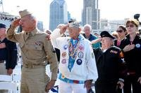 World War II veterans render a hand salute during the parading of the colors during a wreath ceremony held aboard the USS Midway Museum. (U.S. Navy/Nolan Kahn)