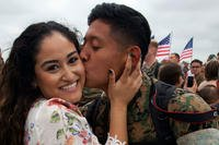 "A Marine with Marine Fighter Attack Squadron (VMFA) 232 ""Red Devils"" reunites with his wife during a homecoming ceremony at Marine Corps Air Station Miramar, California. (U.S. Marine/Shakima DePrince)"