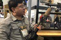 "Magpul engineer Brian Nakayana displays new Magpul 5.5"" suppressor cover. (Hope Hodge Seck/Military.com)"