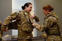 U.S. Army Pvt. 1st Class Cheryl Rogers grins as 2nd Lt. Chelsea Adams helps her into the new Generation III Female Improved Outer Tactical Vest at Fort Stewart, Ga., on Nov. 28, 2012. (U.S. Army photo by Cpl. Emily Knitter)