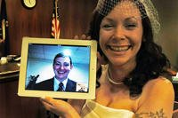 Kari Phelps, spouse of Senior Airman Daniel Phelps, 39th Air Base Wing Public Affairs photojournalist, holds a digital screen of her husband during their online wedding ceremony Oct. 29, 2012. (Courtesy photo)