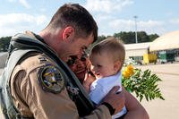captain from the 336th Fighter Squadron greets his family after returning from deployment, April 11, 2018, at Seymour Johnson Air Force Base, North Carolina. Airmen from the 336th FS returned from a deployment in support of Operation Inherent Resolve. (U.S. Air Force/Shawna L. Keyes)