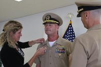 Cmdr. David Dwyer, deputy commander of U.S. Naval Ship Repair Facility and Japan Regional Maintenance Center (SRF-JRMC), is pinned to the rank of captain by his wife, left, and Capt. Garrett Farman, right, the commanding officer. (U.S. Navy photo/Joyce Lopez)
