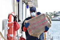 A Coast Guard Cutter Bernard C. Webber crewmember carries a bale of cocaine during a drug offload at Coast Guard Base Miami Beach, Oct. 16, 2018. (U.S. Coast Guard photo/Brandon Murray)