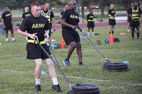 Pfc. Alex Colliver, foreground, pulls a 90-pound sled 50 meters to simulate the strength needed in pulling a battle buddy out of harm's way during a pilot test of the Army Combat Fitness Test, a six-event assessment designed to reduce injuries and replace the current Army Physical Fitness Test. (Photo by Sean Kimmons)