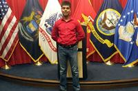 Raheel Siddiqui poses in front of flags for the different branches of the U.S. military. (Photo via Facebook)