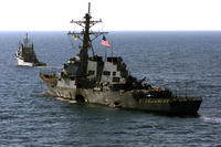 October 29, 2000: The damaged USS Cole is towed to the harbor in Aden, Yemen to await transportation to its homeport by a semi-submersible heavy lift ship. (US Marine Corps photo/Don Maes)