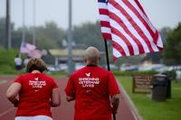 "Tech. Sgt. Jennifer Aucoin, 48th Maintenance Group training manager, runs with her husband, Master Sgt. Jason Aucoin, 48th Fighter Wing ground safety office manager, during a 9/11 Memorial 5K Run/Walk ""Moving Tribute"" at Royal Air Force Lakenheath, England, Sept. 11, 2014. (U.S. Air Force/Airman 1st Class Erin O'Shea)"