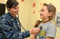 Lt. Cmdr. Michelle Finley, a nurse practitioner with Naval Branch Health Clinic Mayport's Medical Home Port Pink Team, checks Abbigail Engle's heart during a routine exam. (U.S. Navy/Jacob Sippel)