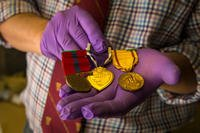 Owen Conner, uniforms and heraldry curator with the National Museum of the Marine Corps, inspects medal collection belonging to U.S. Marine Corps Sgt. Russell Rose at warehouse 2288, Marine Corps Base (MCB) Camp Pendleton, California, Jan. 10, 2019. Several Marine Corps artifacts were collected from the MCB Camp Pendleton History Museum Branch for transport to the National Museum of the Marine Corps in Triangle, Virginia. (U.S. Marine Corps photo/Juan C. Bustos)