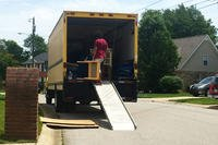 PCS movers putting a small table on a truck