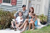 A soldier and his family sits on the front stoop. (Photo: U.S. Army)