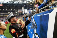 U.S. Marine Sgt. Benjamin J. Annarino signs a fan's helmet during a Detroit Lions football game at Ford Field in Detroit, Oct. 20, 2015. (Photo by: Sgt. J. R. Heins)