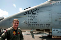 "Lt. Cdr. Michael Tremel stands next to his F/A 18-E Super Hornet on board the USS George W. Bush last July. The tomahawk symbols represent strike missions and the ""kill"" symbol for his shootdown is upper right. (Photo courtesy of Save The Royal Navy)"