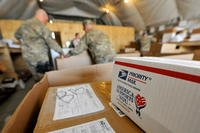 Airmen of the 455th Expeditionary Knowledge Operations Management office sort boxes and envelopes for personnel at Bagram Airfield, Afghanistan. (U.S. Air Force/Senior Airman Chris Willis.)