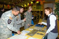 3 soldiers at job fair table