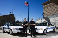 Two police officers and their patrol cars.