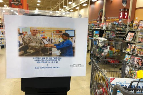 A sign at the Anchorage, Alaska area commissary notifies customers that certain lanes no longer offering bagging services. (Photo: Military.com)