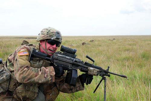 A Soldier assigned to B Co., 2nd Battalion, 5th Cavalry Regiment, 1st Armored Brigade Combat Team, 1st Cavalry Division with a M249 light machine gun charges forward during small arms training at Smardan Training Area, Romania, July 5, 2018. (U.S Army/ Sgt. 1st Class Robert Jordan)