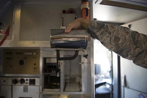 An Airman holds a hot cup inside a KC-10 Extender at Travis Air Force Base, Calif., June 21, 2018. The base is working on developing a new handle for the cup which could save the Air Force thousands. (U.S. Air Force/Tech. Sgt. James Hodgman)