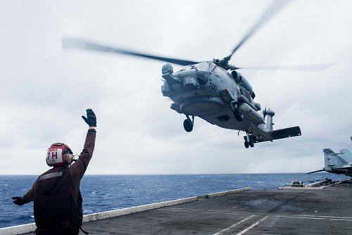 A sailor assigned to Helicopter Maritime Strike Squadron (HSM) 77 directs an MH-60R Sea Hawk as it launches from the flight deck of the Navy's forward-deployed aircraft carrier USS Ronald Reagan (CVN 76) during Valiant Shield 2018, September 20, 2018. (U.S. Navy/Kenneth Abbate)